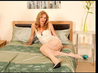Leggy golden-haired cougar copulates herself with a huge sex tool
